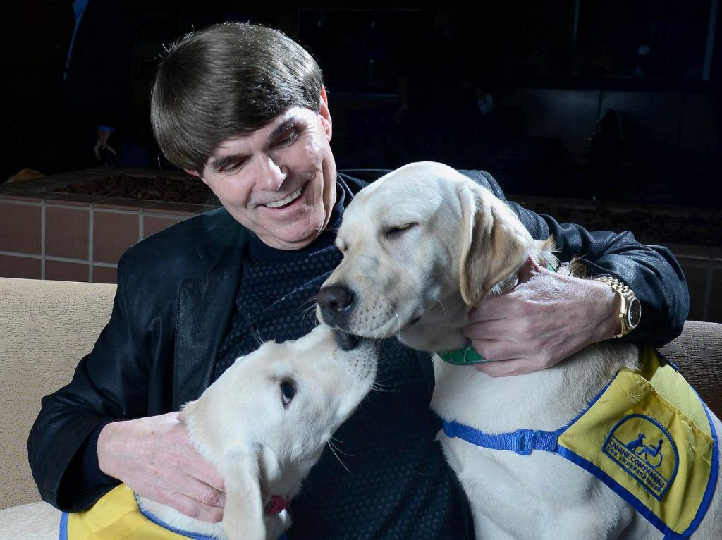 Author Dean Koontz played with two dogs from the Canine Companions for Independence program when he visited the Orange County Register Thursday. The puppy on the left is named Lyric IV. On the right is Deedee. ///ADDITIONAL INFORMATION: 1/14/16 - koontz.0115 - BILL ALKOFER, STAFF PHOTOGRAPHER - Dean Koontz was the most recent author to visit the Orange County Register Book Club. He visited the newspaper on Thursday