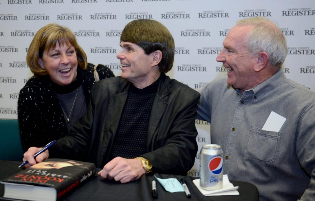 Dean Koontz shared a laugh with Cindy and Jim Vandemoortel after he signed their book Thursday. ///ADDITIONAL INFORMATION: 1/14/16 - koontz.0115 - BILL ALKOFER, STAFF PHOTOGRAPHER - Dean Koontz was the most recent author to visit the Orange County Register Book Club. He visited the newspaper on Thursday